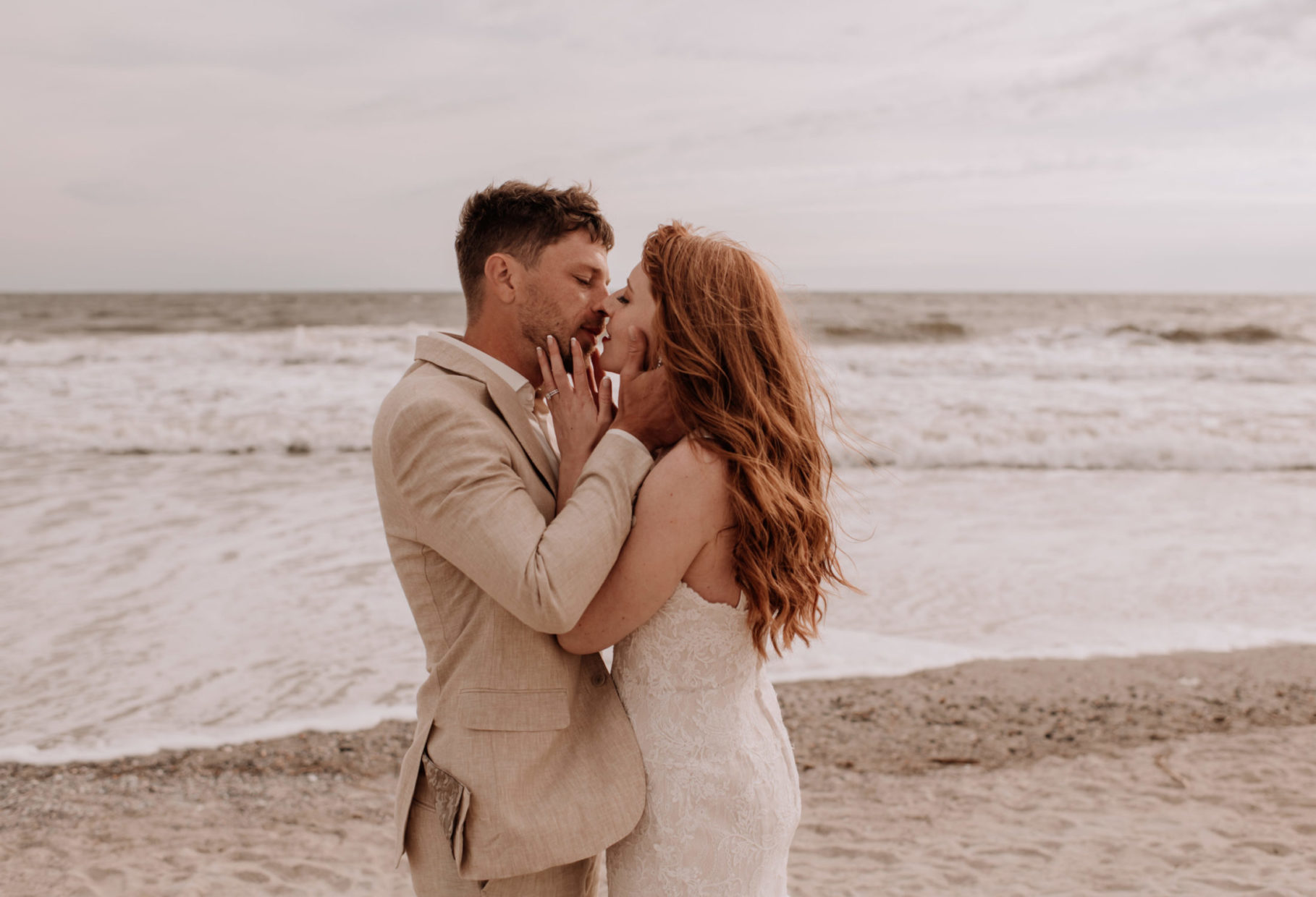 bride and groom kissing next to ocean