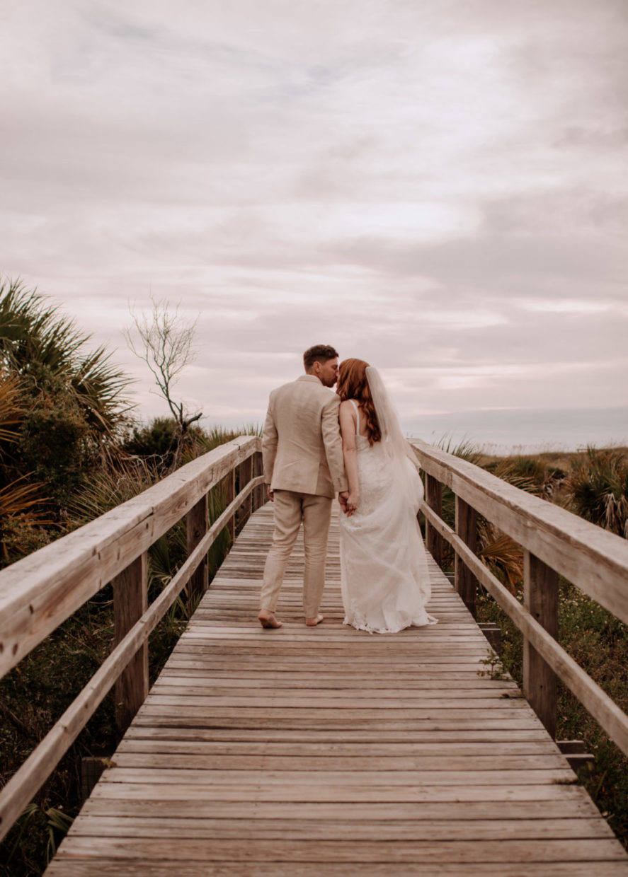bride and groom kissing on boardwalk