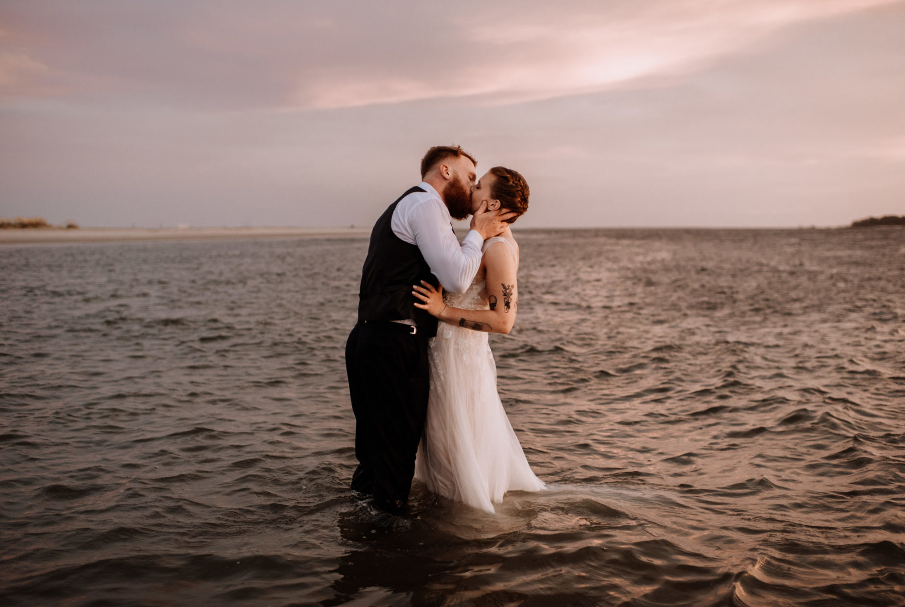 bride and groom kissing in the ocean