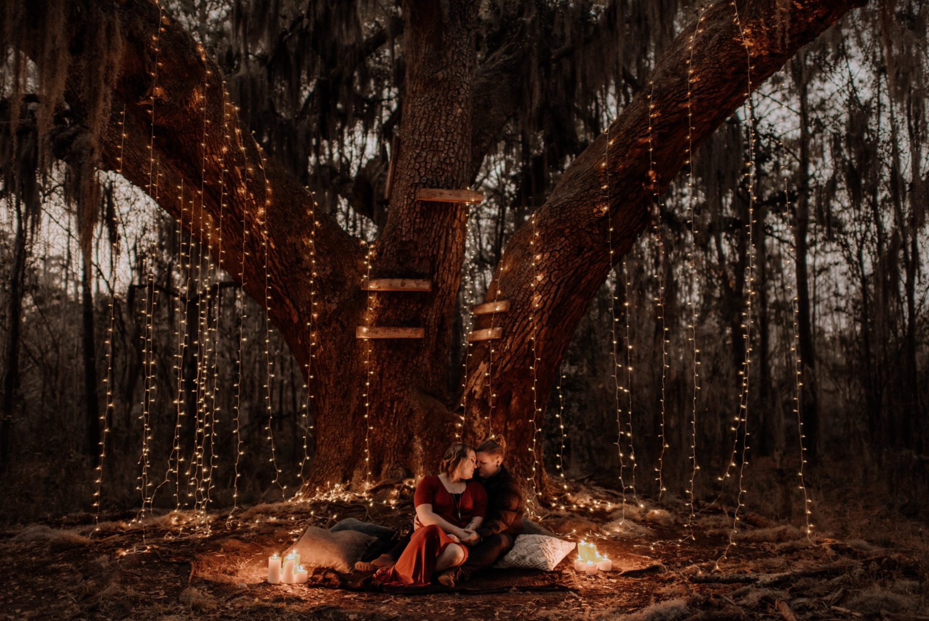 couple sitting under twinkle lights