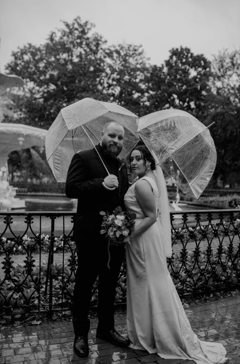 bride and groom holding umbrellas